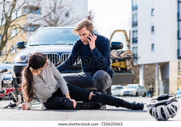 Vollständige Ansicht eines besorgten jungen Fahrers, der den Krankenwagen anruft, nachdem er versehentlich ein weibliches Fahrrad auf einer Stadtstraße getroffen und verletzt hat