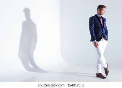 full length view of a young business man looking away while holding a hand in his pocket. on a gray background with shadow