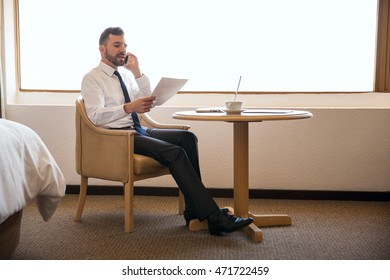 Full length view of a young business manager talking to a client on a smartphone and doing some work in a hotel room during a business trip