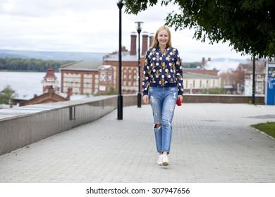 Full length, walking happy blonde woman in autumn park