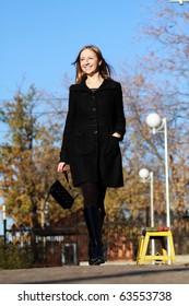 Full length, walking woman in autumn park