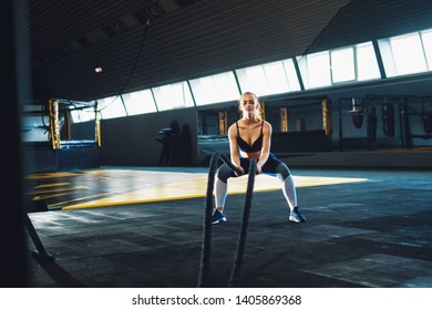 Full length wide angle shot of a young woman working out with battle ropes.  Copyspace background with athletics healthy composition.