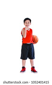 Full length of winner asian child celebrating success with his hand raised.  Athlete boy in sportswear smiling and looking at camera with a basketball at studio. Isolated on white background.