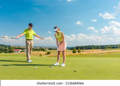 Full length of a woman calculating the trajectory of the ball to the hole, while playing professional golf with her male match partner or instructor outdoors in summer
