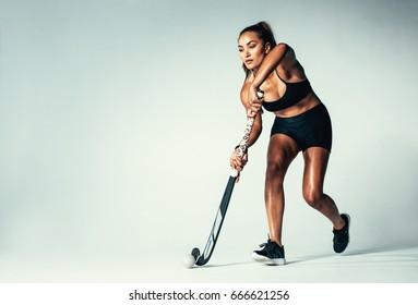 Full length of woman hockey player dribbling ball on grey background. Hispanic female playing hockey in studio.