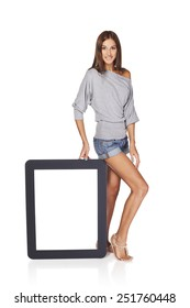 Full length woman showing blank empty screen with copy space. Happy caucasian girl standing with tablet frame over white background