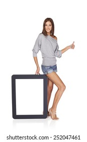 Full length woman showing blank empty screen with copy space. Happy caucasian girl standing with tablet frame and gesturing thumb up sign, over white background