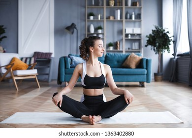 Full length woman sitting in lotus position in living room. Balance and meditation.