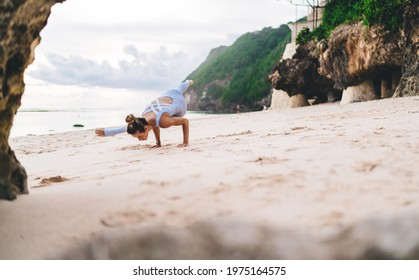 Full length of woman standing in Ashtavakrasana pose on sandy coast while stretching legs and strengthening hands and muscles of spine
