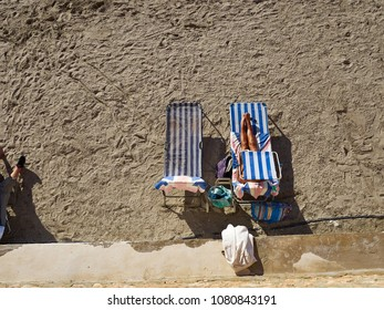 Full length a woman sun bathing loungers on sea sand by the ocean great summer time