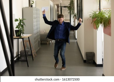 Full length worker celebrating successful negotiations ending, make deal dancing in office hallway raised hands feels happy. Lucky applicant, after job interview, got new work, hired promoted concept