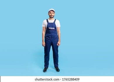 Full length worker man in blue overalls and cap standing, looking calm and positive at camera. Profession of service industry, house repair. indoor studio shot isolated on blue background