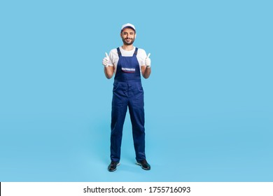 Full length workman in overalls, cap and protective gloves standing, showing thumbs up, like gesture and smiling, recommending good house repair services. studio shot isolated on blue background