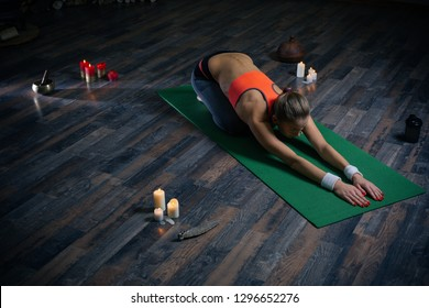 Full length of yoga training and young woman bending to the ground while practicing asana on the yoga mat with candles around her