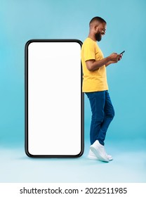 Full length of young Afro guy using cellphone while leaning on giant mobile phone with empty white screen, blue studio background. Mockup for app or website, space for advertisement - Shutterstock ID 2022511985