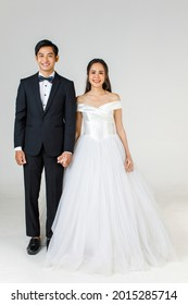 Full Length of young attractive Asian couple, soon to be bride and groom, woman wearing white wedding gown. Man wearing black tuxedo, standing together. Concept for pre wedding photography.