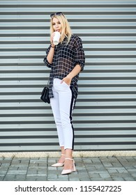 Full length young beautiful excited woman with gorgeous natural lips, blue and brown eyes in black blouse having fun with disposable white cup on urban metal strips background