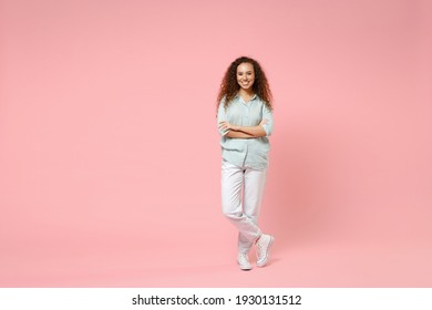 Full length young black african american happy smiling positive curly woman 20s wearing blue casual shirt looking camera hold hands crossed folded isolated on pastel pink background studio portrait