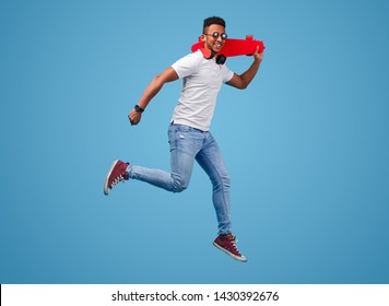 Full length young black man with longboard smiling and leaping against blue background