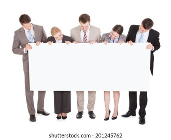 Full length of young business people looking at blank billboard over white background
