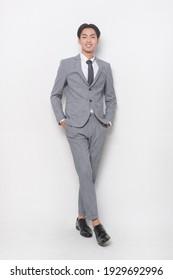 junger Geschäftsmann mit grauem Anzug, Krawatte mit weißer und grauer Hose, schwarze Schuhe mit Studioaufnahme