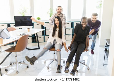 Full length of young businesspeoples pushing colleague in chair at empty office
