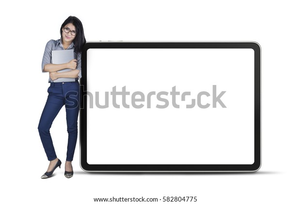 Full length of young businesswoman leaning on big board while holding a laptop, isolated on white background
