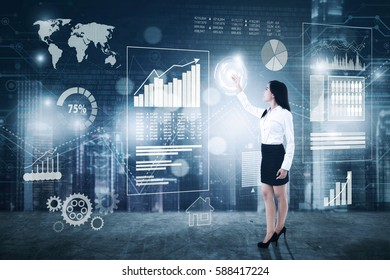 Full length of young businesswoman touching virtual button with financial statistics on the digital screen