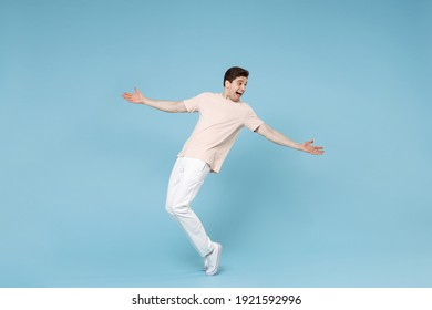 Full length of young caucasian attractive smiling student man 20s in beige t-shirt white pants leaning over with outstretched hands looking aside isolated on blue color background studio portrait.