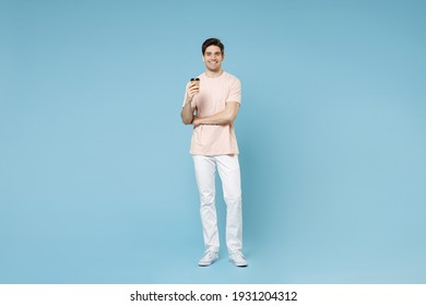 Full length of young caucasian attractive happy smiling student man 20s in beige t-shirt white pants hold paper cup of hot coffee drink look camera isolated on blue color background studio portrait