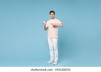 Full length of young caucasian happy smiling gladden student man 20s wearing beige t-shirt white pants holding point index finger on mobile cell phone chat isolated on blue background studio portrait