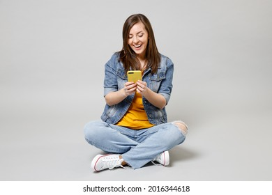 Full length young caucasian woman 20s in casual denim jacket yellow t-shirt use mobile cell phone browsing sitting cross-legged isolated on grey background studio portrait. People lifestyle concept.
