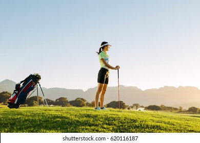 Full length of young caucasian woman standing on golf course on a summer day. Female golfer holding golf club on field.