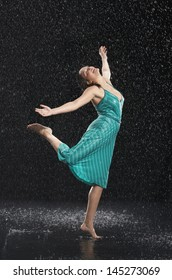 Full length of a young cheerful woman with arms out dancing in rain