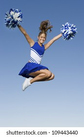 Full length of a young cheerleader jumping against clear sky