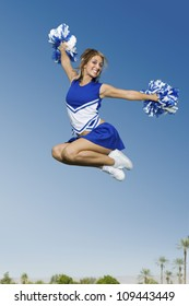 Full length of a young cheerleader jumping with pom-poms against sky