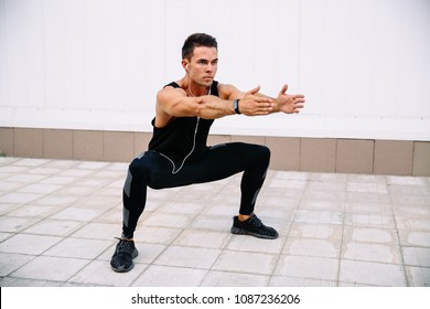 Full length of young concentrated sportsman doing squats during workout outdoors, listening to music in earphones. Wearing black sportswear. Healthy lifestyle.