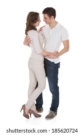 Full length of young couple in casuals embracing isolated over white background