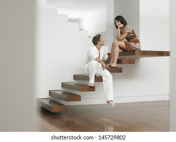 Full length of a young couple sitting on stairs in house