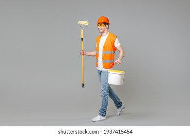 Full length young employee man in orange vest protective hardhat stand hold paint bucket roller walking isolated on grey background studio. Instruments for renovation apartment. Repair home concept