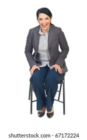 Full length of young executive woman sitting on chair and laughing out loud isolated on white background