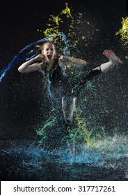 Full Length of Young Fierce Red Haired Woman Performing High Kick While Being Splashed with Colorful Water in Dark Studio with Black Background