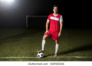 Full length of young football team player standing with his foot on the soccer ball outdoors on field