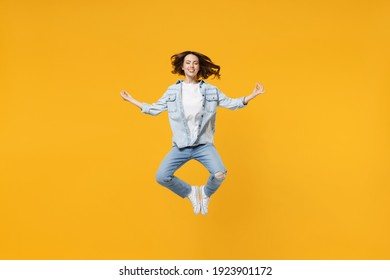 Full length of young fun happy spiritual woman 20s wear denim shirt white t-shirt hold hands in yoga gesture relax meditate try to calm down levitating isolated on yellow background studio portrait.