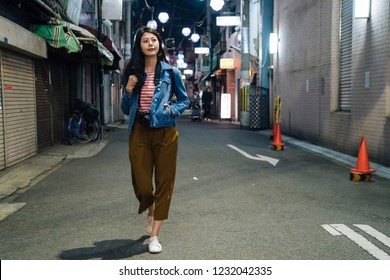 full length of young girl in brown trousers walking by path in city. businesswoman after work going back to home at night. quiet street with traffic cones beside the houses.