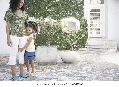 Full length of young girl hugging mother's leg in yard