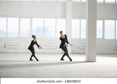 Full length of young girl learning ballet from her instructor in empty warehouse