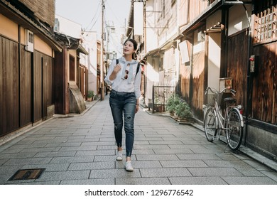 full length of young girl travel backpacker walking on road in ishibe alley kyoto japan. japanese old history town hosue made of wooden and bamboo. bike stop in street near the mail box.