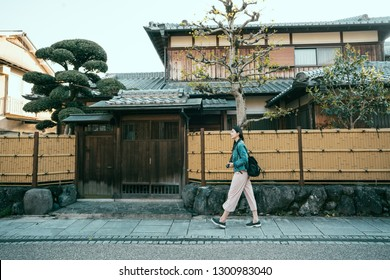 full length of young girl travel photographer walking along the bamboo walls of japanese style wooden house with trees and graden inside. woman backpacker on street road in town city kyoto japan.