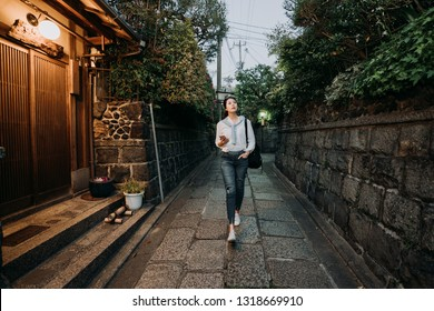 full length of young girl visitor walking alone in little path in old historical town in kyoto japan. lady traveler holding mobile phone finding hotel in Ishibe alley. beautiful asian woman relaxing.